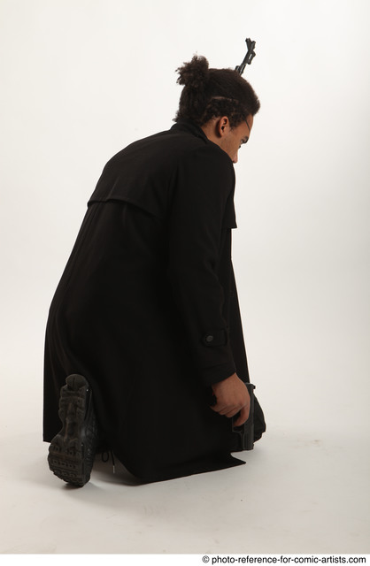 Man Adult Average Black Fighting with gun Sitting poses Coat