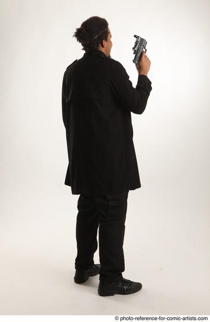 Man Adult Average Black Fighting with gun Standing poses Coat