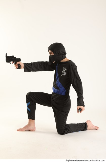 Man Young Athletic Fighting with gun Kneeling poses Casual Asian